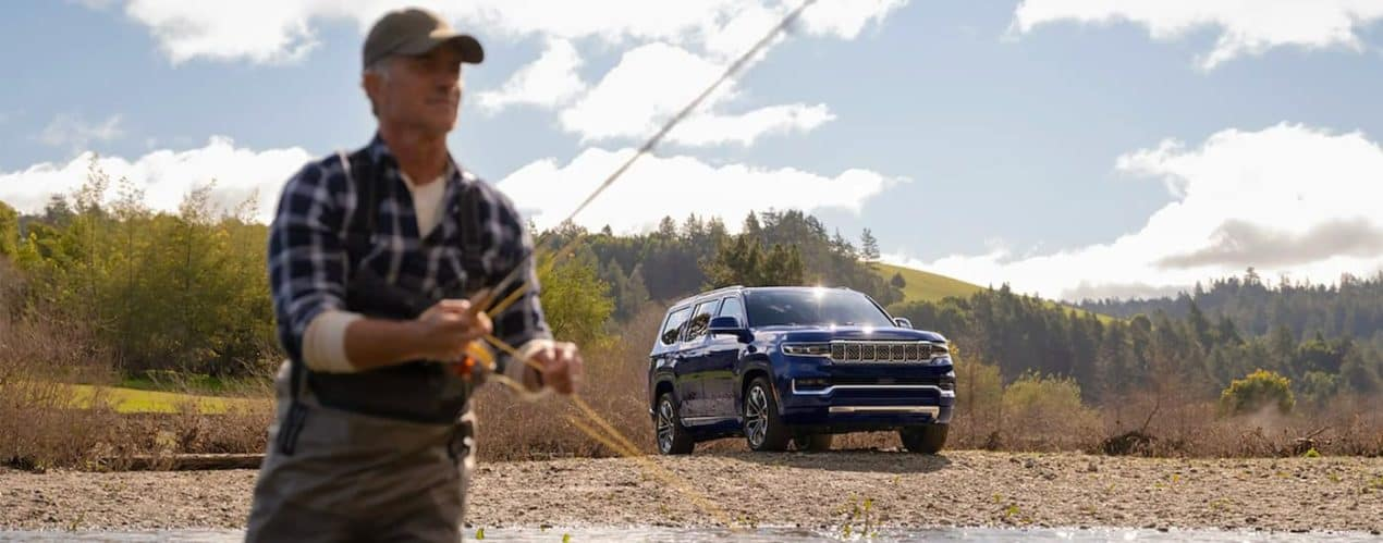 A dark blue 2022 Wagoneer is shown parked on a river bank with a man in the foreground fly fishing.