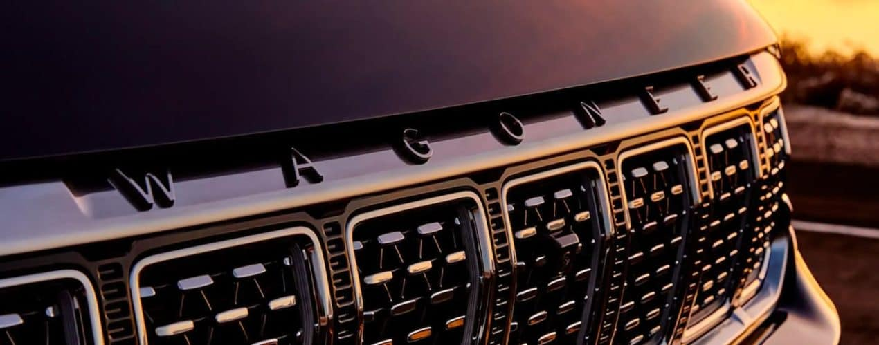 A close up shows the front grille and badging on a black 2022 Wagoneer.