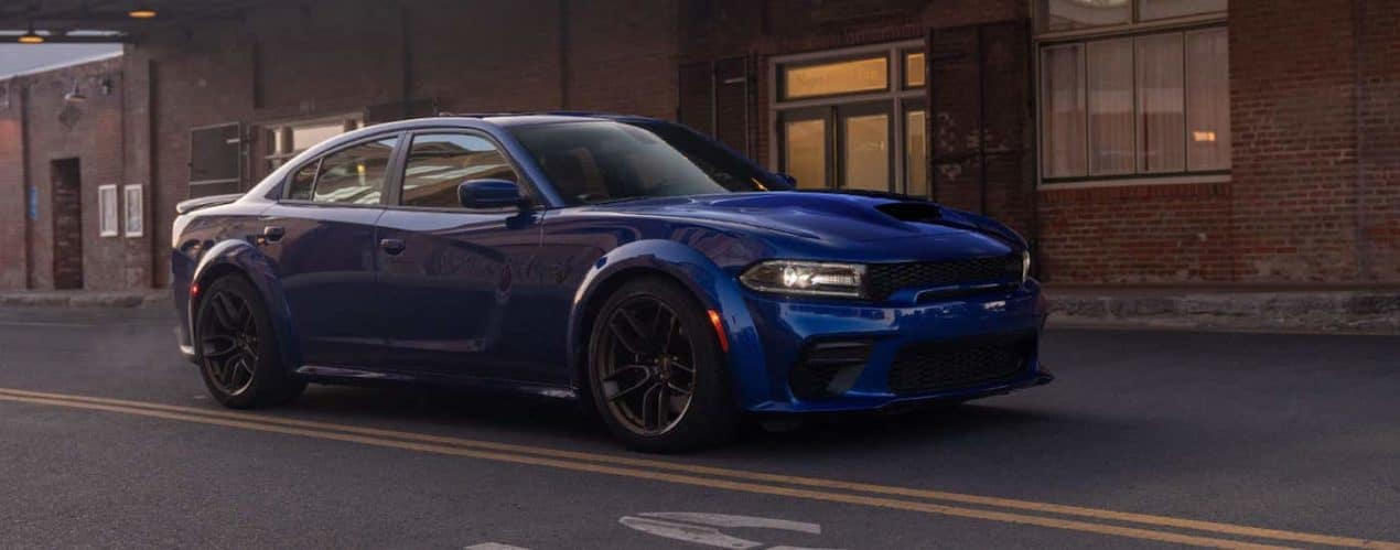 A blue 2021 Dodge Charger GT is shown parked in front of a brick building.