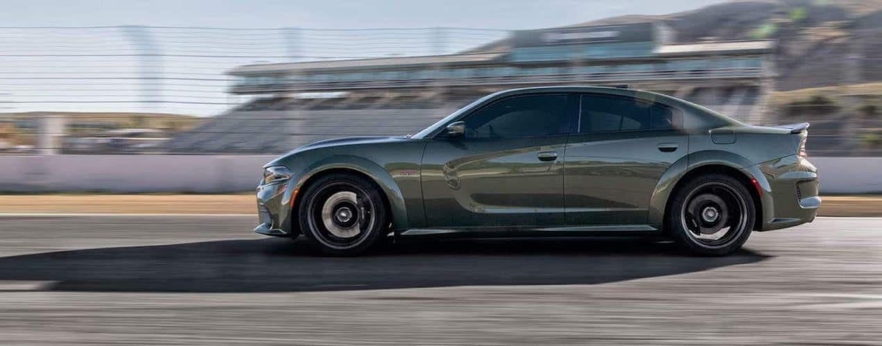 An olive green 2021 Dodge Charger is shown from the side driving down a track.