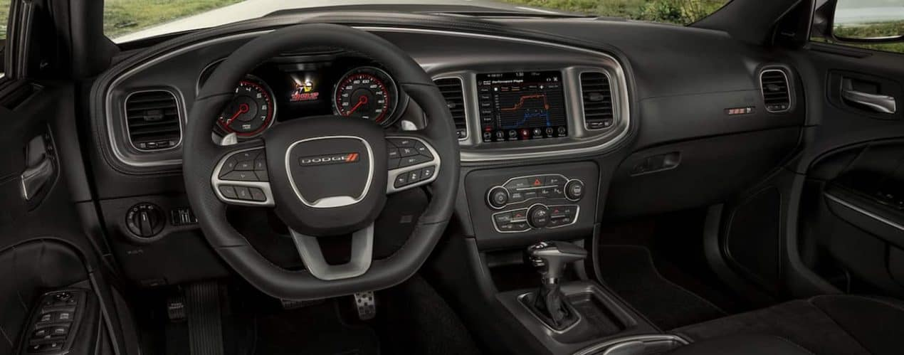 The black interior of a 2021 Dodge Charger shows the steering wheel and infotainment screen.
