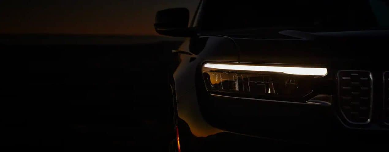 A close up shows the headlight and DRL on a 2021 Jeep Grand Cherokee L.