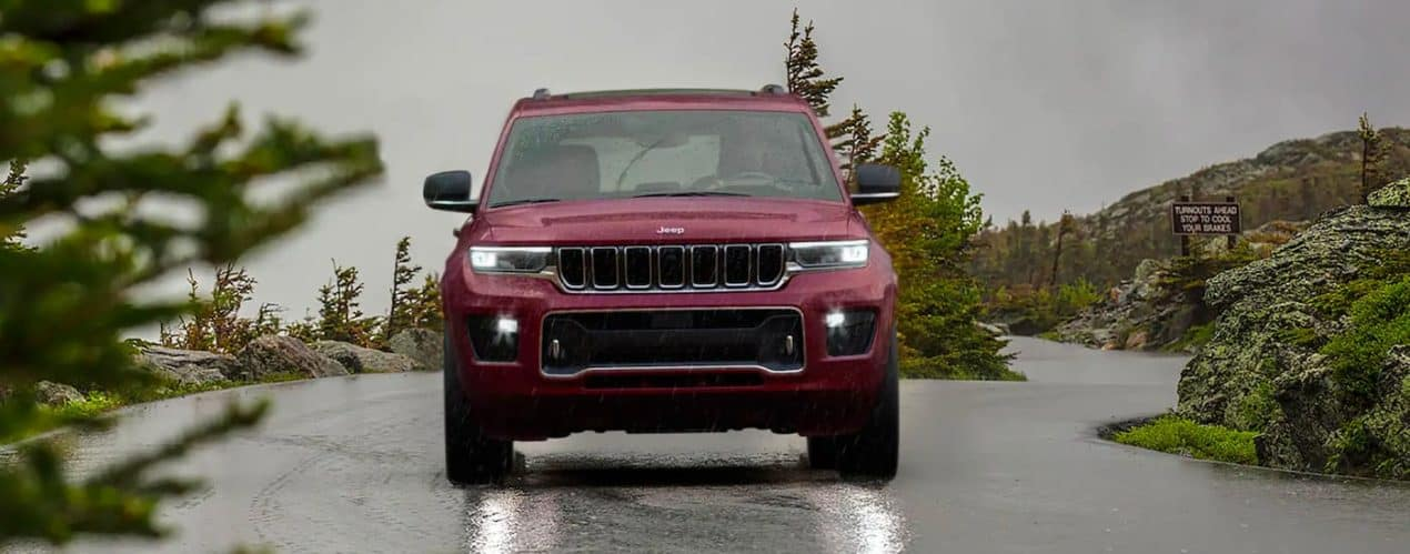 A red 2021 Jeep Grand Cherokee L is shown driving down a wet mountain road after winning the 2021 Jeep Grand Cherokee L vs 2021 Chevy Traverse comparison.