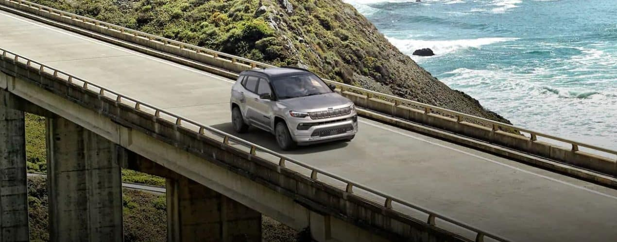 A grey 2022 Jeep Compass is shown driving over a bridge.