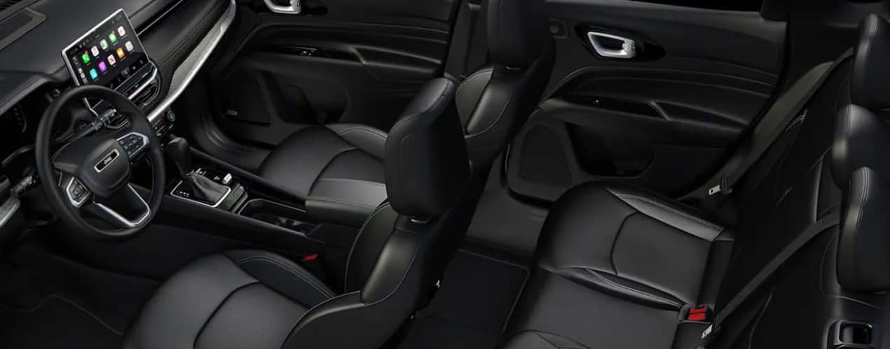 The black interior of a 2022 Jeep Compass shows the steering wheel and two rows of seating.