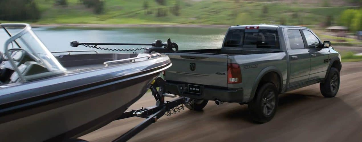 A grey 2022 Ram 1500 is shown towing a boat.