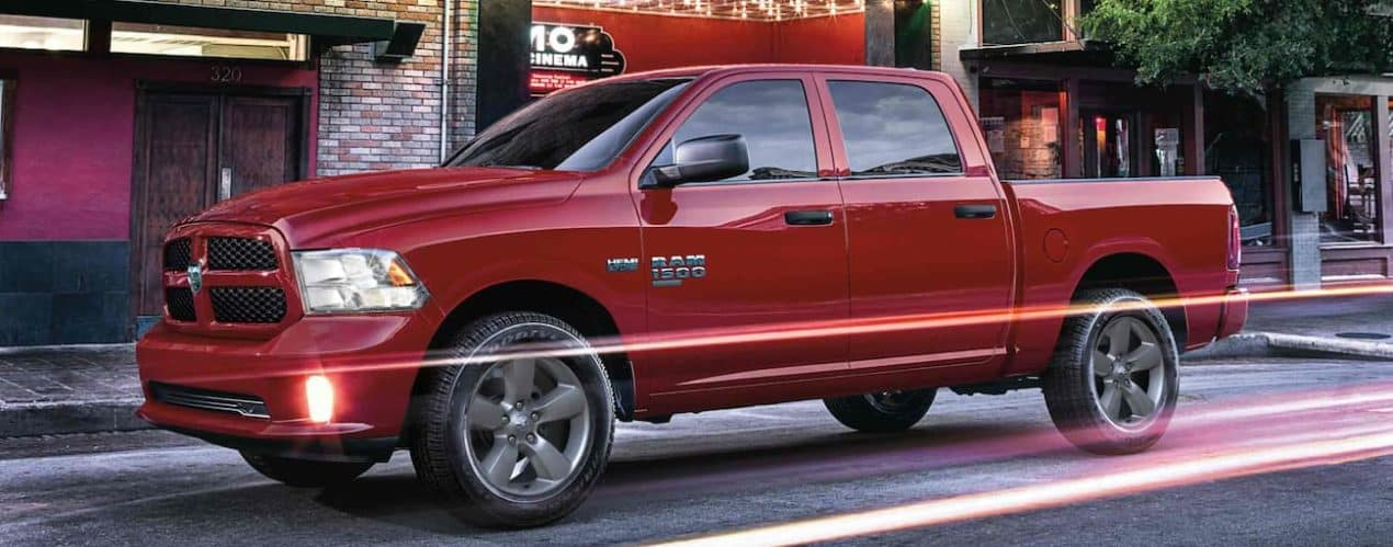 A red 2022 Ram 1500 is shown parked on a city street.