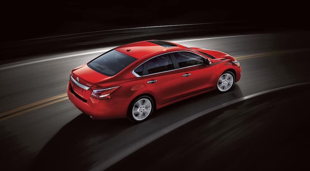 Red 2019 Nissan Sentra driving on black background
