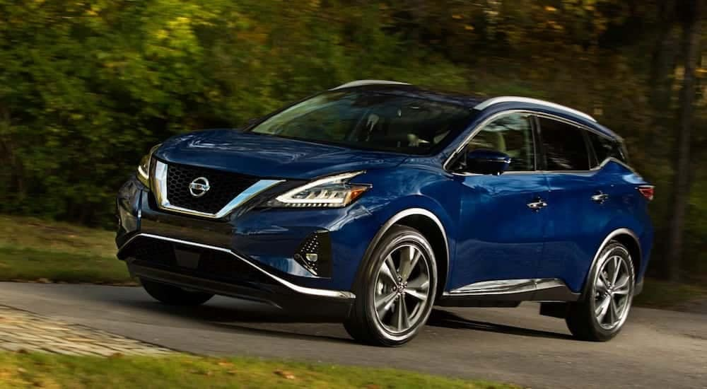 A blue Nissan model Murano on a test drive on a quiet street