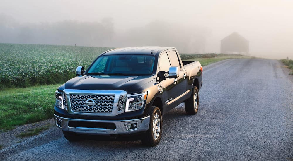 A black 2019 Nissan Titan in a field clouded by early morning fog