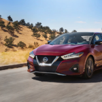 A red 2019 Nissan cruises the California hills outside Huntington Beach
