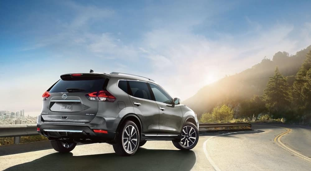 A silver 2019 Nissan Rogue parked on a sunset lit mountain road