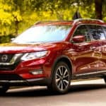 A red 2019 Nissan Rogue is parked in a tree-lined neighborhood. The Rogue is a great option if you need a Nissan in Huntington Beach.
