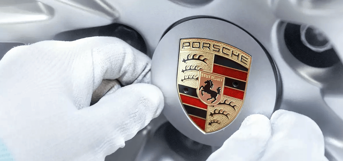 Porsche logo and insignia being installed on car wheel rim during manufacturing