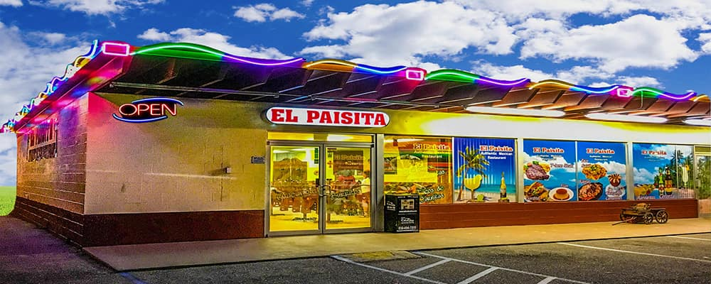 Front view of El Paisita Mexican restaurant featuring a multi-colored neon light design on the roof