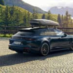 Black Porsche Cayenne with a canoe rack on top of it parked in front a bright mountain scene