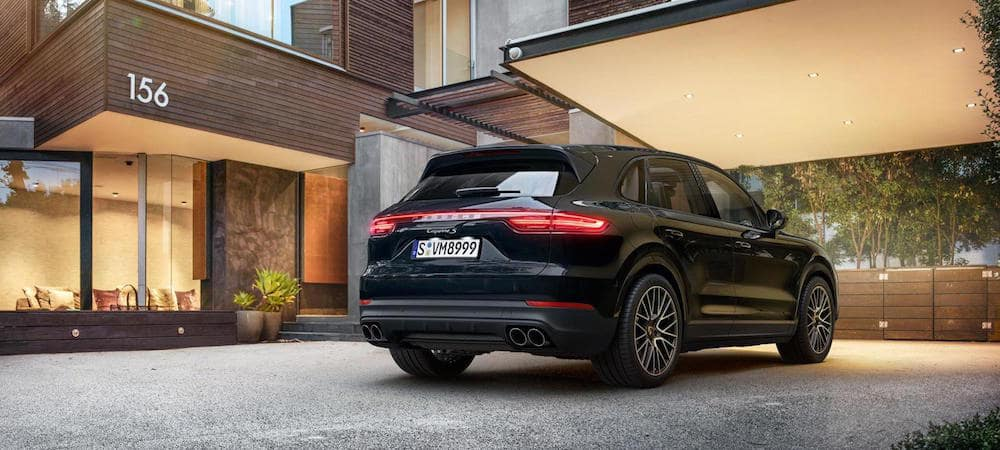 Black Porsche Cayenne parked in front of a building