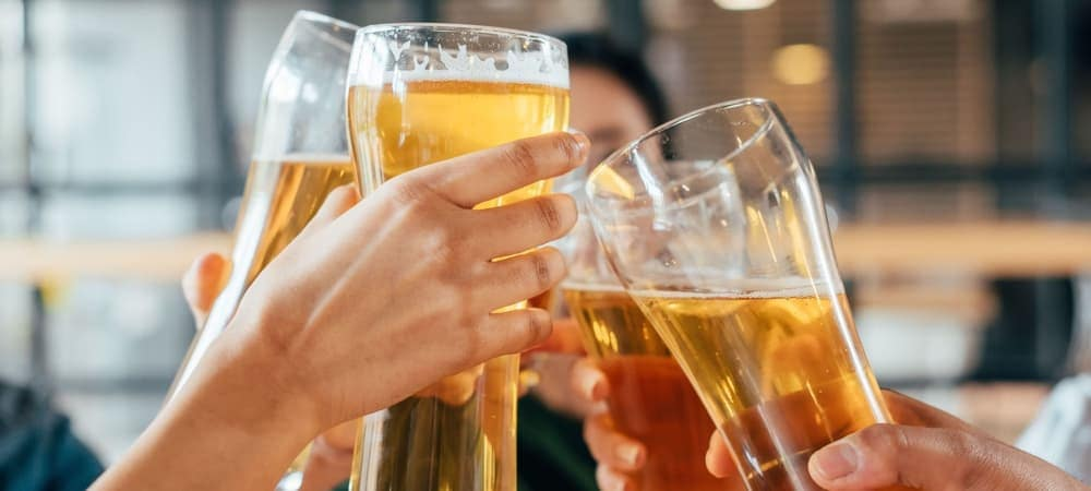 Friends clinking with beer in cafe