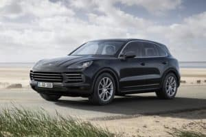 Image of a black 2019 Porsche Cayenne parked at the beach.