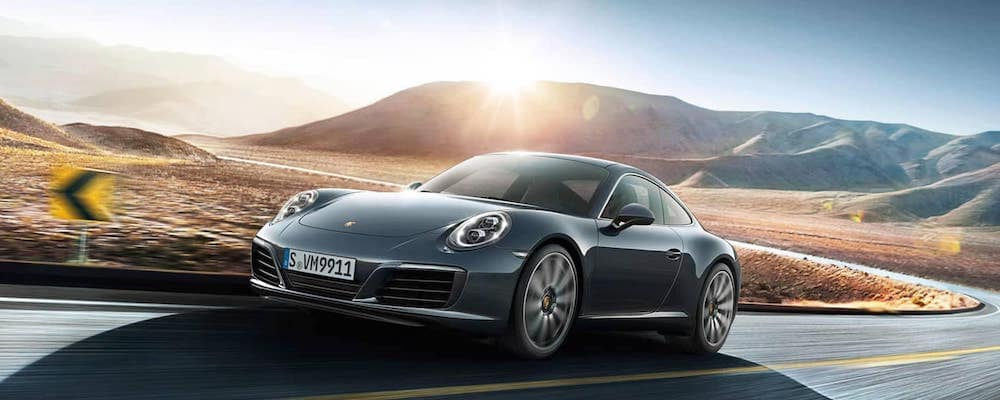 Gray metallic 2019 Porsche 911 Carrera driving on highway with mountains and sun in background