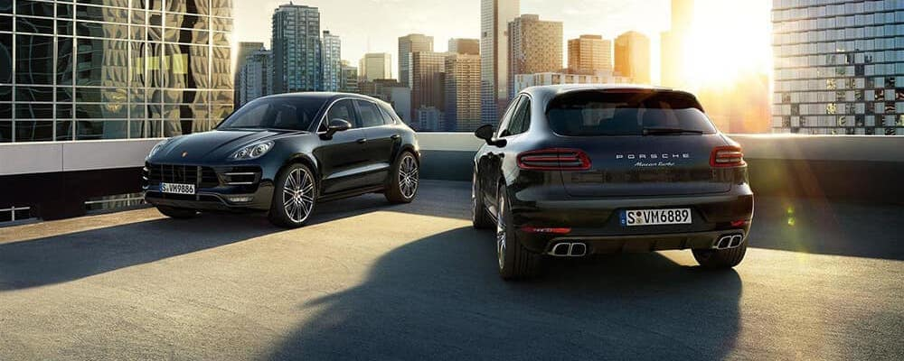 Two 2019 Porsche Macan Turbo models parked on roof with city skyline and sunbeam in background