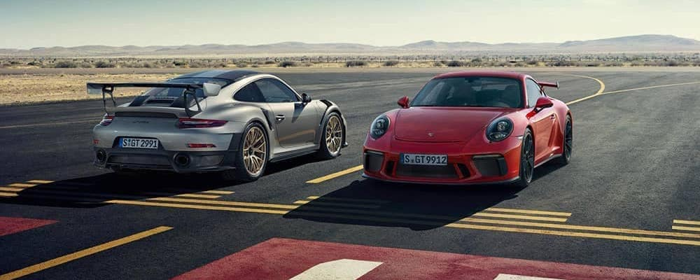 Silver and Red 2019 Porsche 911 models on runway in the desert. Porsche Top Speeds concept.