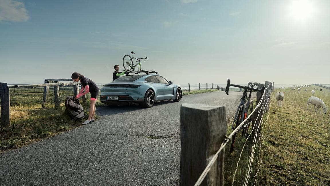 Porsche Taycan on country road with cyclists