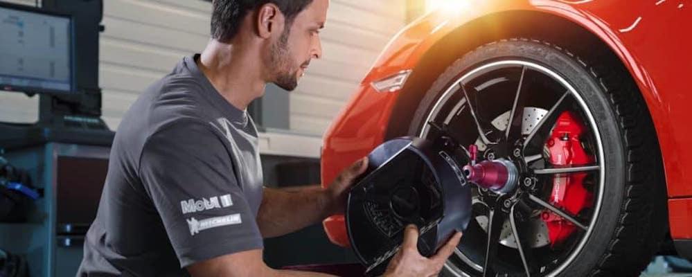 Porsche service technician working on wheel of vehicle