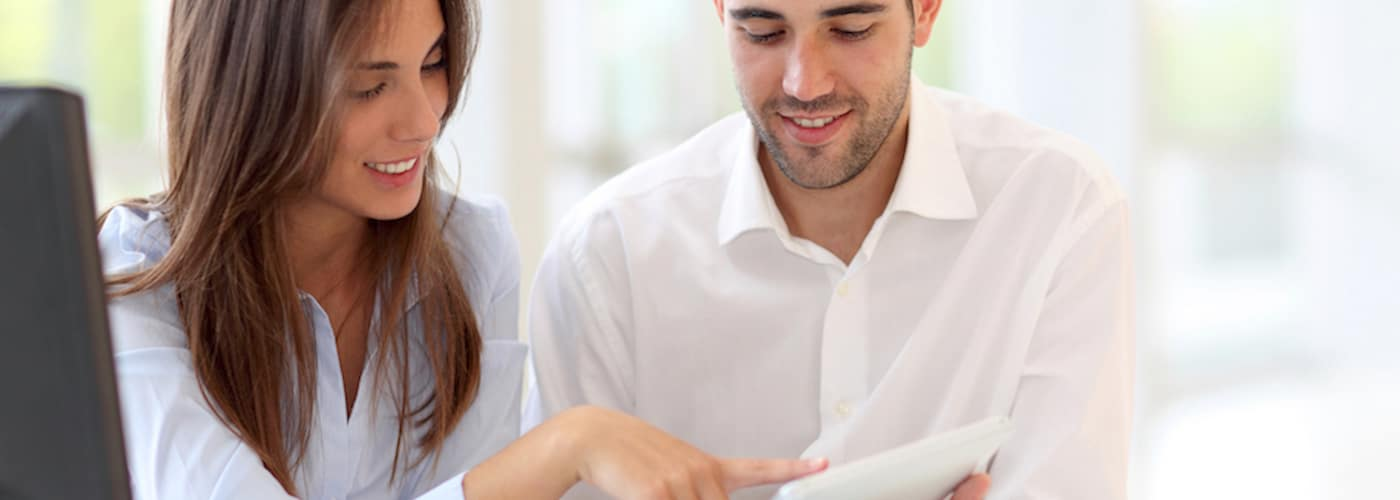 Couple looking at touchpad at home