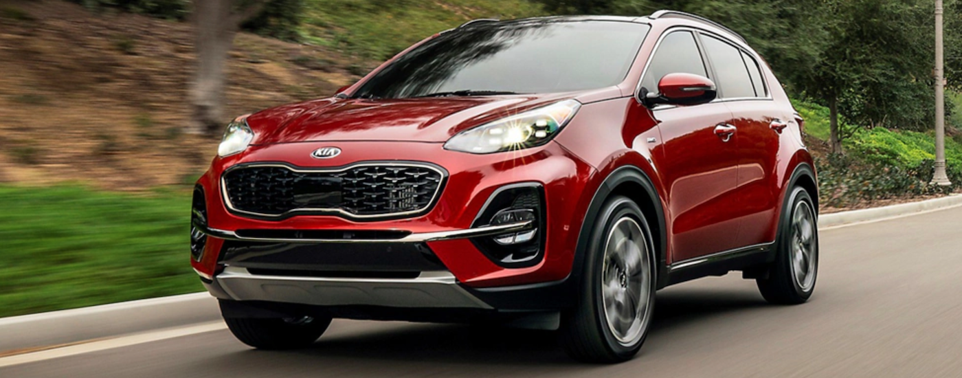 2020 kia sportage red exterior driving down road in daylight