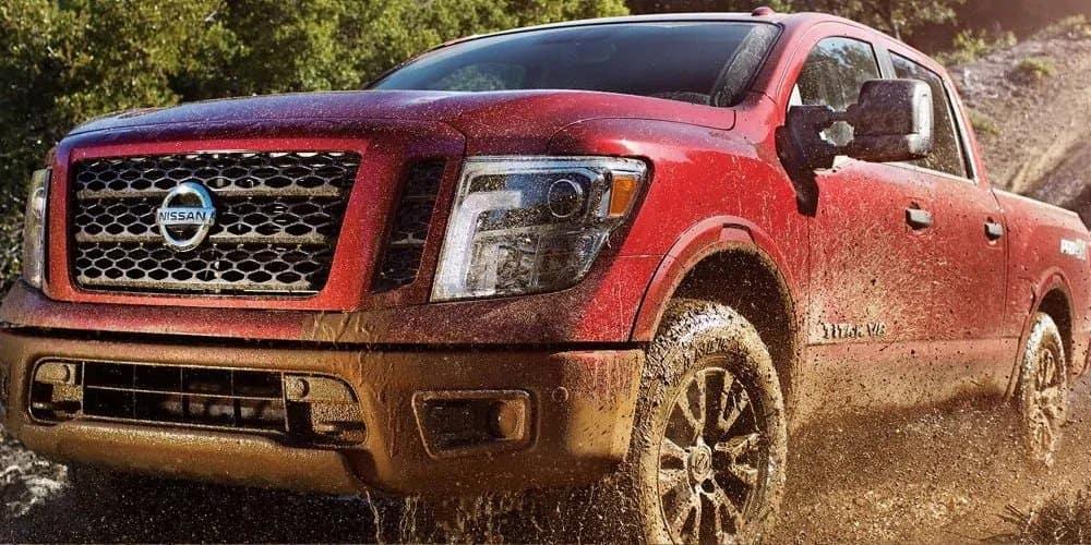 Red 2019 Nissan Titan Driving Through Mud