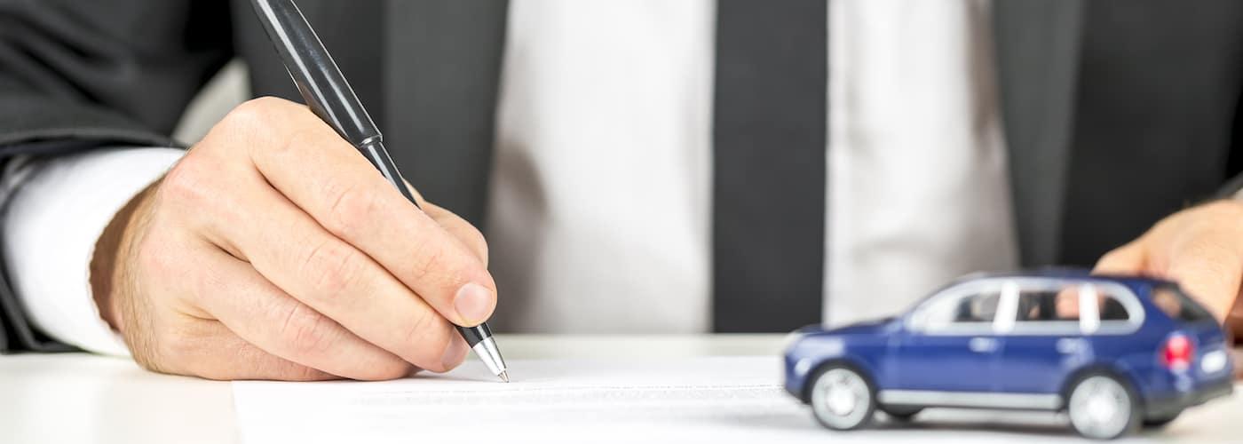 Man Signing Contract at Car Dealership