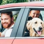 Family Inside Red Car With Golden Retriever Looking Out Window