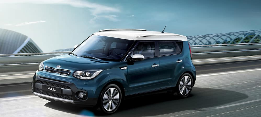 Blue Kia Soul with white roof driving on highway
