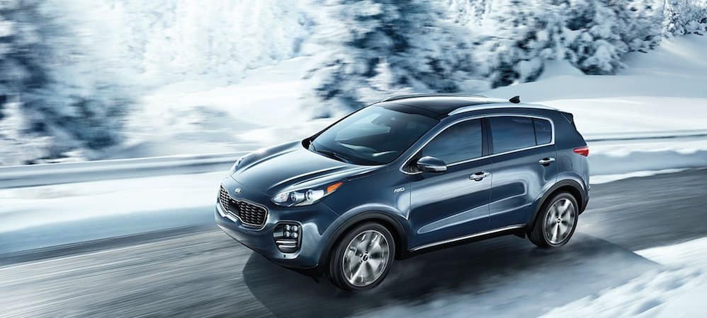 Kia Sportage driving on icy road in winter time