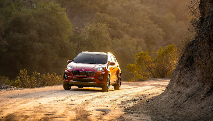 Red 2020 Kia Sportage driving up mountain road