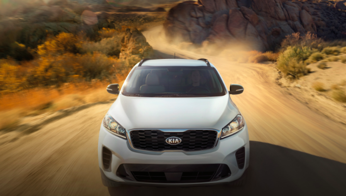 White Kia Sorento driving down a desert road