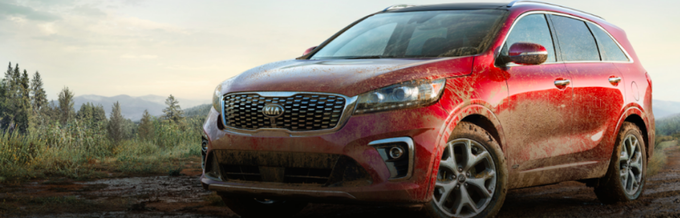 Red Kia Sorento with front end and tires covered in mud