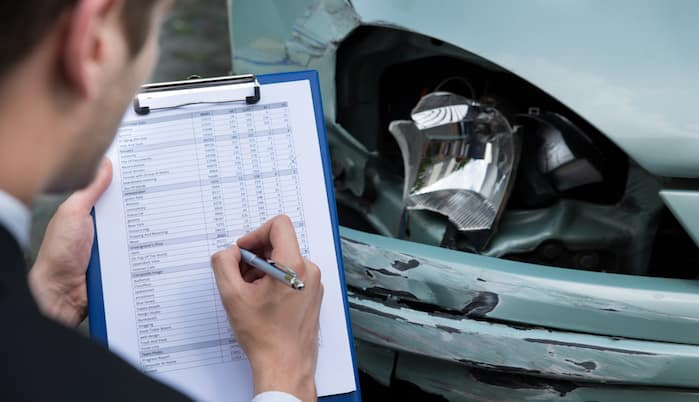 Insurance agent assessing headlight damage on car