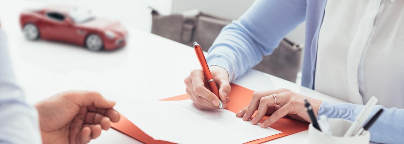 Woman signing car insurance paperwork
