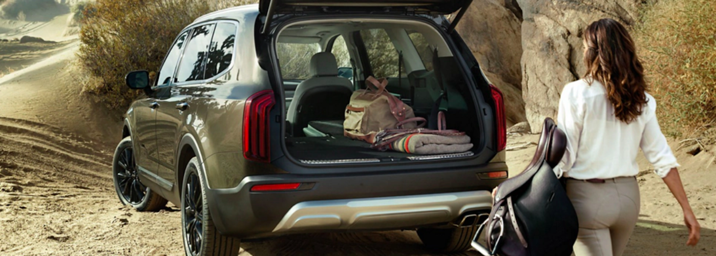 Woman approaching Kia Telluride with open liftgate
