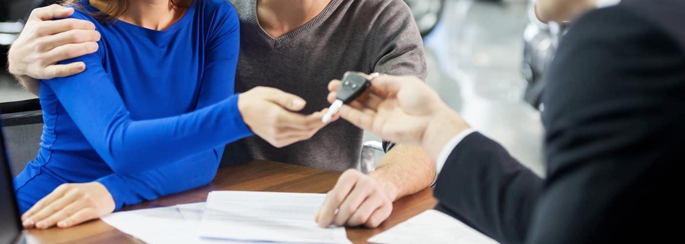 car salesman handing a car key to a couple