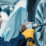 Mechanic removing lug nuts from tire using a tool