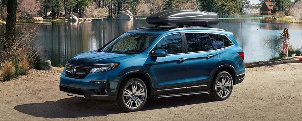 Blue 2019 Honda Pilot parked by a lake