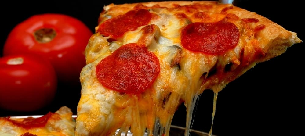 Slice of pepperoni pizza being removed from whole pizza with tomatoes in background.