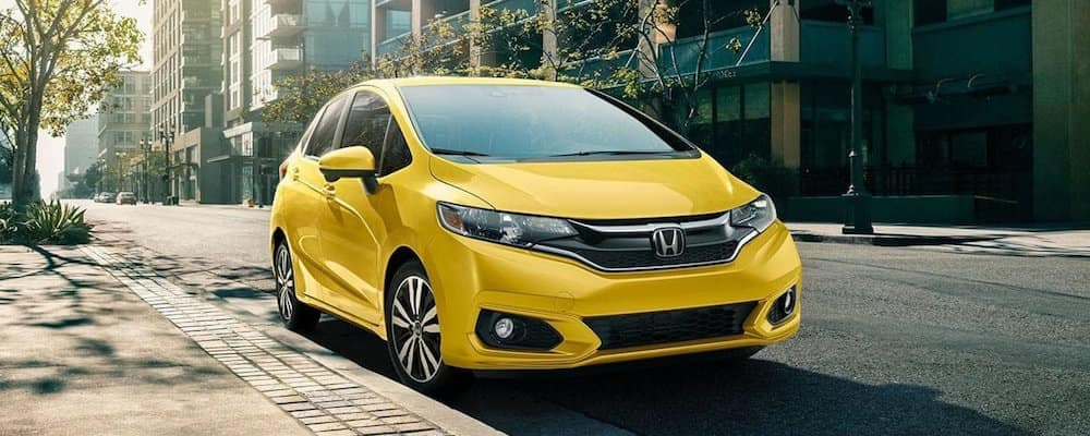 Yellow Honda FIt parked on curb