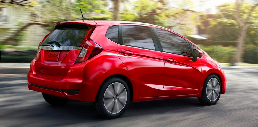 Red Honda Fit driving