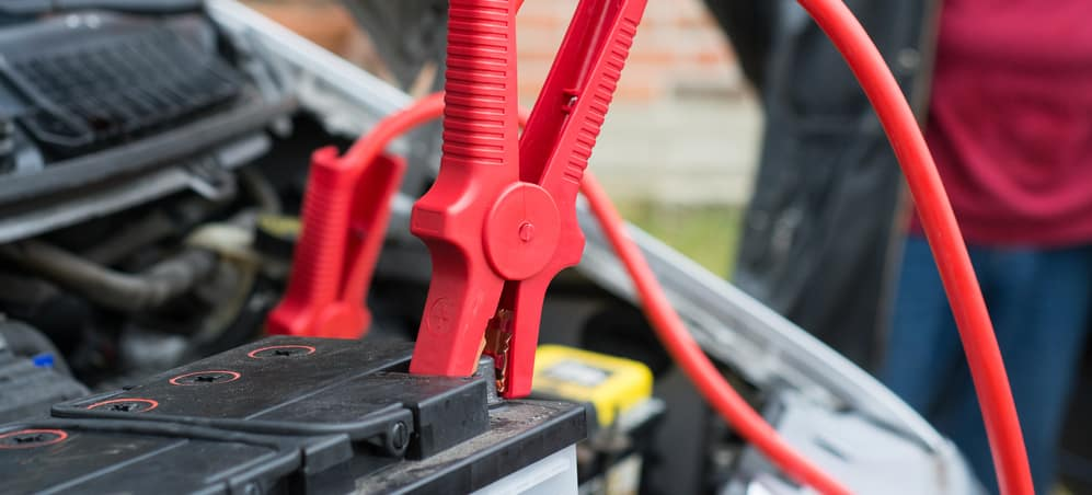 car battery clamped with red jumper cable