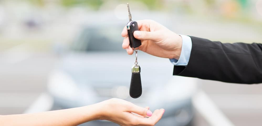 Woman buying a car and sales person handing her car keys